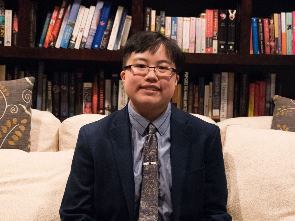 A young East Asian person with glasses and short black hair smiles directly at the camera. They are wearing a dark blue suit and paisley tie, and sitting on a couch in front of an arching bookcase. Photo by Katie Miller.