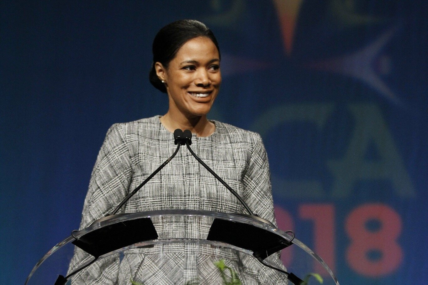 An African American woman with black hair in a low bun smiles at the camera. She is standing behind a podium with a microphone wearing a black and white, plaid, long sleeve dress.