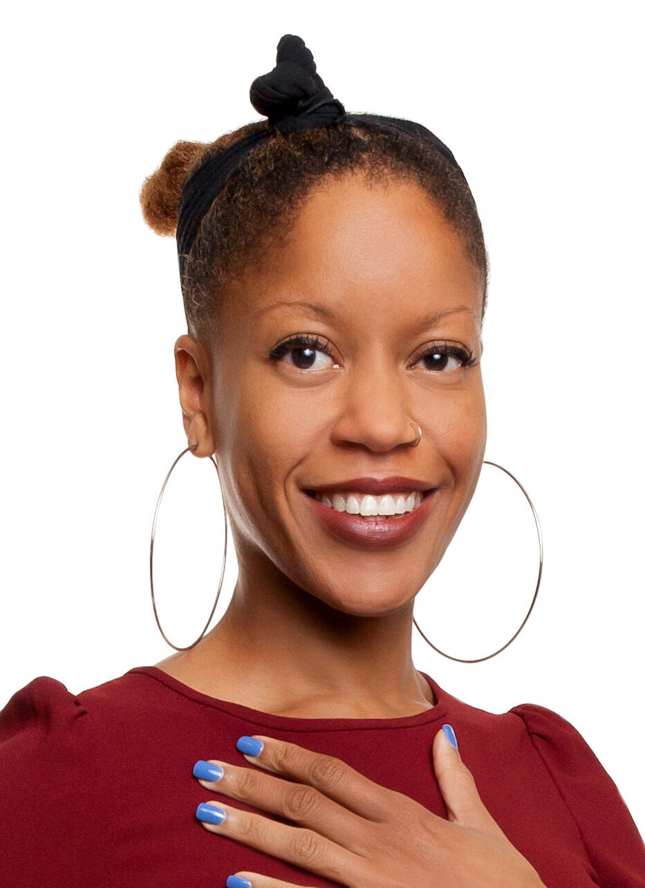 A Black woman with a gold hoop nose ring and dark red lipstick stares directly at the camera, smiling. She has light brown curly hair in a bun and wears a black headband tied in a knot. She is wearing a dark red blouse that matches the lipstick color and large gold hoop earrings. She has one hand laid flat on her chest, showing her periwinkle blue nail polish.
